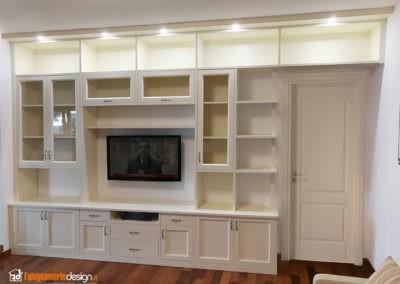 Soggiorno con mobile in legno per tv e parete attrezzata con faretti